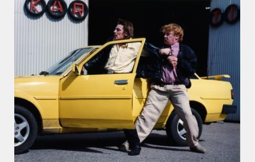 Kiilopää (Janne Hyytiäinen) ja Kartio (Matti Onnismaa) välienselvittelyssä. Kartio häipyy autolla, jolloin Kartio hälyttää poliisit hänen peräänsä.
