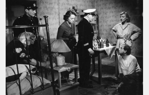 Rouva Södergran (Kerttu Salmi, sängyllä) on löytynyt. Muut vasemmalta: poliisi (Arvo Kuusla), Anna-Liisa Raikas (Eila Peitsalo), Oton isä Antti Markkanen (Olavi Virta), alamaailman nainen Sylvi (Irja Rannikko) ja tämän miesystävä (Einari Ketola).