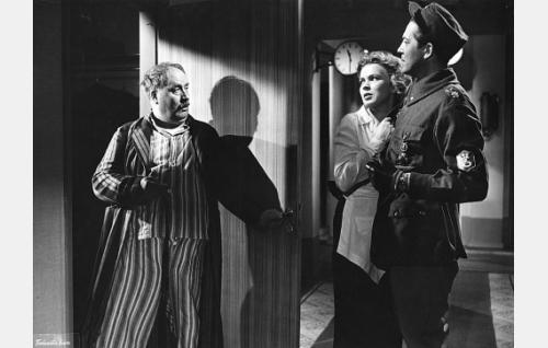 Elmer Oras (Erkki Viljos, oik.) pelastaa Margitin (Tuija Halonen) liikemies Mähkiön (Veikko Linna) lähentely-yritykseltä.