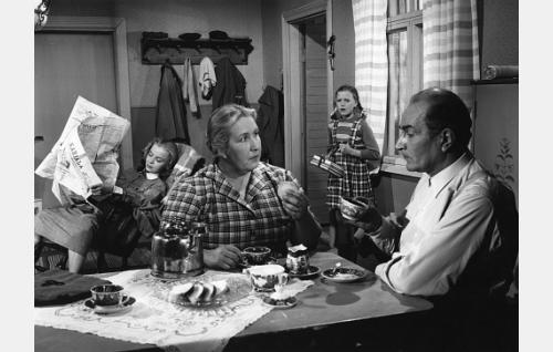 Pöydän ääressä Nikkasen Ulla (Linda Lampinen) ja Nikkasen Aato (Santeri Karilo). Taustalla heidän tyttärensä Elvi (Aino-Maija Tikkanen, vas.) ja Sirkka (Eila-Kaarina Roine).