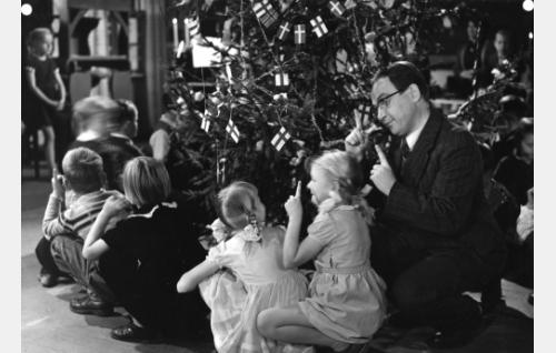 Kansakoulunopettaja Torvald Allnes (Leo Riuttu) laulattaa oppilaitaan. Lapset ovat tunnistamattomia.