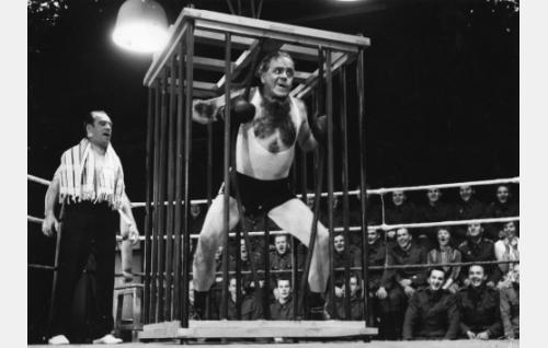 Nyrkkeilyottelussa maavoimia edustava Kalle Kovanen (Einari Ketola) on tuotu kehään häkissään. Vasemmalla hänen kehäavustajansa (Heimo Lepistö).