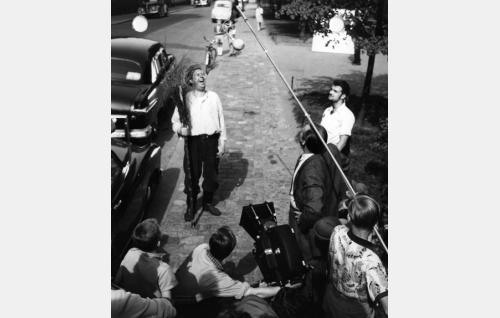 Talonmies Pikkarainen (Armas Jokio) on vilpittömän (vahingon-)iloinen. Kameran vasemmalla puolen kamera-assistentti Veikko Mård, takana kuvaaja Mikko Sergejeff. Äänityspuomia pitelee äänitysassistentti Keijo Iiskola. Puomin alla seisoo ohjaaja Armand Lohikoski. Oikealla kuvausryhmän jäsen Orma Aunio.