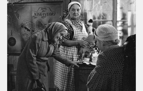 Telefooni-Sandra (Martta Kinnunen) mielistelee Niskavuoren vanhaa emäntää (Elsa Turakainen). Taustalla seuraa tilannetta sisäkkö-Eeva (Ida Salmi).