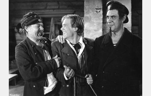 Jaanan isä, merimies Niko (Holger Salin, oik.) on pukeutunut etsintäkuulutetuksi rosvoksi ja antautunut vangiksi Eskon enolle Sakerille (Matti Lehtelä, vas.) ja veljelle Iivarille (Ernest Ervasti).