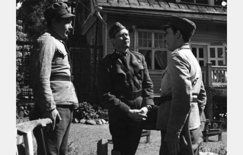 Alokkaat Puustinen (Lasse Pöysti) ja Kervinen (Tommi Rinne) kapteenin (Hannes Häyrinen, keskellä) juttusilla.