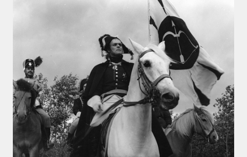 """Kenraali Sandels (Leif Wager) valkoisen """"Bijou-ratsunsa"""" selässä. Taustalla vasemmalla luutnantti (Tarmo Manni) ja Sandelsin takana hänen adjutanttinsa (Matti Oravisto)."""