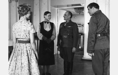 Sisäoppilaitoksen rehtori Hildur (Elsa Turakainen) ja kenraalimajuri Hjalmar (Santeri Karilo) ovat vanhoja tuttuja. Oikealla kapteeni Routa (Helge Herala), vasemmalla voimistelunopettaja Marjatta Paasi (Marjatta Kallio.