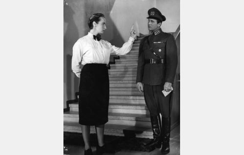 Maisteri Järvi (Marja Korhonen) pitää puhuttelua kapteeni Roudalle (Helge Herala).