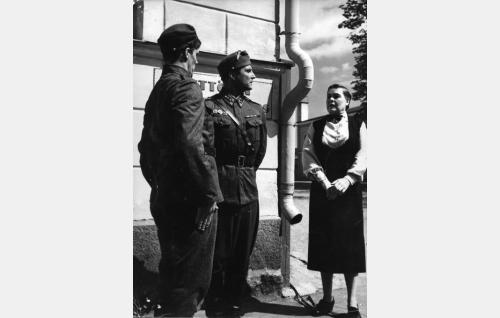 Sotamies Pöntinen (Tommi Rinne) ja kapteeni Tauno Routa (Helge Herala) ovat tavanneet Hildurin, sisäoppilaitoksen rehtorin (Elsa Turakainen).
