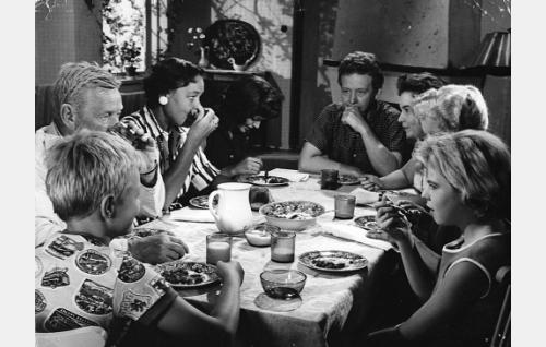 Suomisen väki aterialla. Vasemmalta Matti (Jyrki Lappi-Seppälä), Volmar-vaari (Arvo Lehesmaa), äiti (Elsa Turakainen), Laura Sorri (Elina Salo), Olli (Lasse Pöysti), Pipsa (Maire Suvanto), Karin-mummu (Eine Laine) ja Marja (Ulla-Riitta Jämsä).