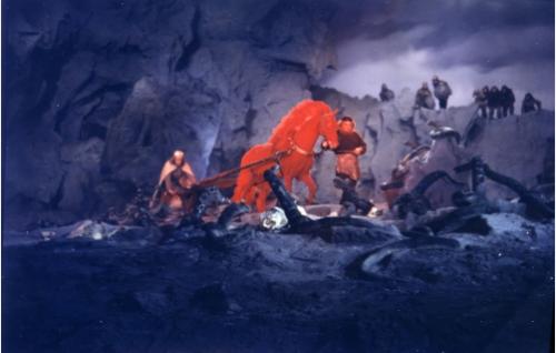 Ilmarinen (Ivan Voronov) on takonut raudasta hevosen ja auran, joilla Lemminkäinen (Andris Oshin) kyntää kyisen pellon.