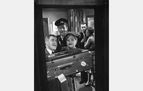 William Makinen (Edvin Laine) ja Lilli Sorjanen (Elsa Turakainen) lähdössä sormuksia ostamaan. Tapahtumaa todistaa poliisi (Vilho Ruuskanen). Taustalla nuoripari Kaija (Liisa Tuomi) ja Otto (Jussi Jurkka).
