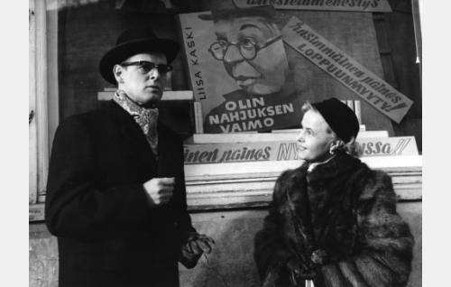 Maisteri Kaarlo Kaski (Leif Wager) tapaa tutun rouvan (Laila Rihte) kirjakaupan edessä.