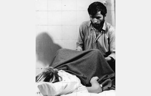 Yövartija (Yrjö Tähtelä) auttaa naista (Aila Kokkila) synnytyksessä.