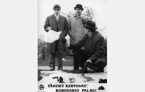 Etsivä (Tauno Söder) esittelee murhapaikalta löytyneitä tavaroita ensimmäisen ryhmän päällikölle tuomari Virralle (Matti Ranin, vas.) ja komisario Palmulle (Joel Rinne).