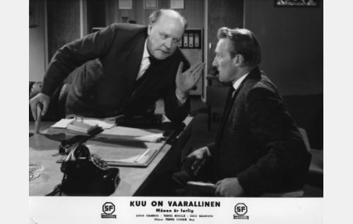 Kauppias Tuomainen (Eero Roine) ilmoittaa nimismies Hermanssonille (Åke Lindman) poikansa kadonneen.