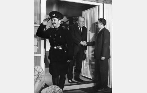 Kauppias Tuomainen (Eero Roine, keskellä) on saapunut Sten Lehtojan (Toivo Mäkelä, oik.) huvilalle konstaapeli Kokkosen (Kaarlo Wilska, vas.) kanssa tiedustelemaan salaperäisellä tavalla kadonnutta poikaansa.