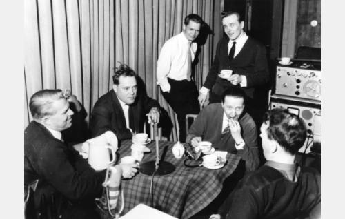 Elokuvan äänitystä Suomi-Filmin studiossa. Pöydän ääressä istumassa vasemmalta Lasse Hjort, Paavo Noponen, Olavi Puusaari ja Matti Kassila. Taustalla olevia ei ole tunnistettu.