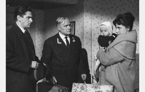 Pikku-Matti (Ari-Pekka) on päässyt äitinsä Ritva Mäkisen (Heidi Krohn, oik.) syliin. Vasemmalla arkkitehti Matti Koskinen (Matti Ranin), keskellä Matkakoti Rauhalan yövahtimestari Ripatti (Eino Kaipainen).