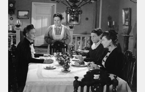 Pöydässä istumassa Hedvig Björn  (Elsa Turakainen, vas), häntä vastapäätä Sofia Björn  (Siiri Angerkoski) ja Raakel Björn  (Verna Piponius). Pöydän takana seisoo emännöitsijä Anna (Elna Hellman).