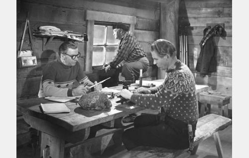 Istumassa Joel Rinne ja Kullervo Kalske, ikkunan ääressä Aku Korhonen.