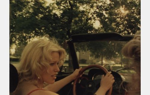 Ulla (Riitta Käpynen) avoauton ratissa, kyydissä istuu Titta, Penan vaimo (Pirjo Siiskonen).
