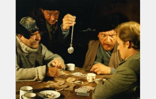 Taskukello pelipanoksena korttiringissä. Vasemmalta Laukunperän Ville (Risto Mäkelä), tunnistamaton. Arpinaama (Leo Lastumäki) ja Vikke Nilo (Jyrki Kovaleff).