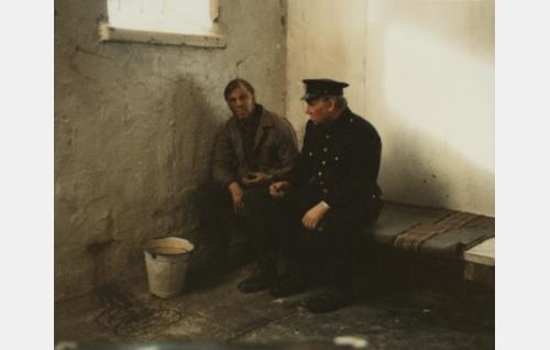 Poliisi Portimo (Ahti Kuoppala) jututtaa sellissä mylläri Gunnar Huttusta (Vesa-Matti Loiri).