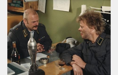 Komppanianpäällikkö (Jyrki Kovaleff) ja Uuno (Vesa-Matti Loiri) sopivat ylennyksestä.