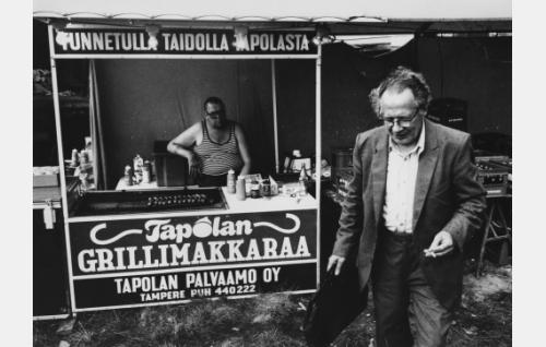 Makkarakauppias ja asiakas Ellivuoren juhannusjuhlilla.