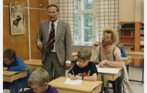 Peruskoulun opettaja (Helge Herala) ja koululuokka. Oppilaiden joukossa Uuno Turhapuro (Vesku Loiri).