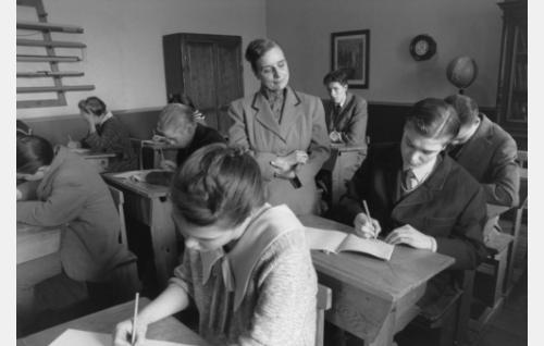 Saksan opettaja (Stina Svensson) seuraa Erik Lindbergin (Carl-Gustaf Wentzel) kirjoitustyöskentelyä.