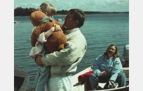 Reeta (Maria Liljelund) löytää meren rantaan ajelehtivan lelukarhun, Uppo-Nallen. Molemmat ovat isän (Juha Muje) sylissä. Äiti (Laura Jurkka) ja perheen koira istuvat veneessä.