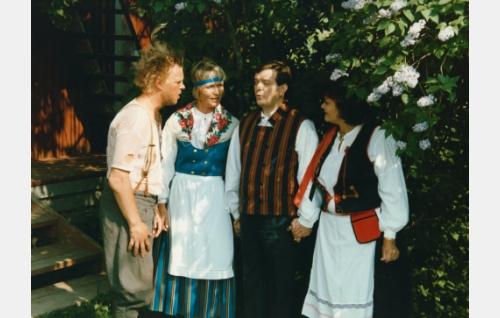 Uuno Turhapuro (Vesku Loiri), Elisabeth Turhapuro (Marjatta Raita), Paavo (Paavo Väyrynen) ja johtaja Tuuran vaimo (Marita Nordberg) kesäjuhlassa.