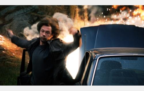 Vareksen (Antti Reini) auto räjähtää. Kuva: Solar Films Inc. Oy.
