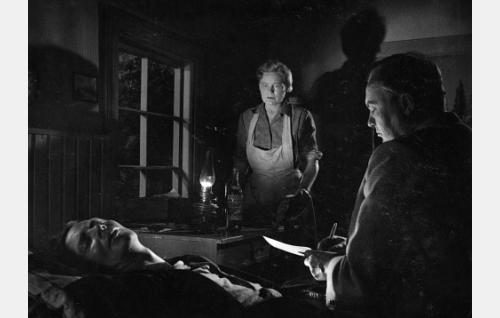 Lääkäri (Severi Seppänen, oik.) on todennut Viktor Sundvallin (Toivo Mäkelä) kuolleeksi. Keskellä Saima Sundvall (Emma Väänänen).