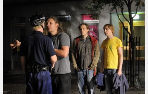 Henninen (Eero Milonoff) sanailee nuorelle poliisille (Tuukka Huttunen),  Marsalkka (Jussi Nikkilä) ja Lihi (Ylermi Rajamaa) seuraavat tilannetta. Kuva: Jolle Onnismaa.