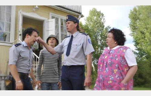 Poliisi Mutka (Jukka Rasila) vääntää Reppanaista (Timo Kahilainen) nenästä, Jaakko Kakelberg (Atte Reunanen) ja Liisa Kakelberg (Satu Säävälä) seuraavat sivusta. Kuva: Malla Hukkanen / Jackpot Films Oy.