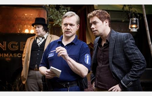 Poliisimies Jori (Puntti Valtonen) ja Repe (Tatu Siivonen), taustalla Hippo (Tuomas Uusitalo).
