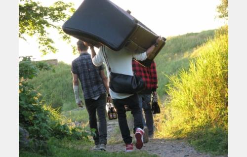 Karri (Henrik Mäki-Tanila), Pete (Anton Thompson Coon, sohva harteillaan) ja André (Karim Al-Rifai) matkalla kaljoittelemaan merenrantaan. Kuva: Elina Manninen.