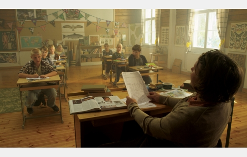 Kyläkoulun opettaja (Eero Milonoff, selin) sekä oppilaat Pukari (Eetu Julin), Tuukka (Artturi Auvinen), Pate (Jyry Kortelainen), Tiina (Aura Mikkonen), Ella (Freja Teijonsalo), Hanna (Emilia Paasonen) ja Samppa (Aki Laiho). Kuva: Snapper Films Oy.