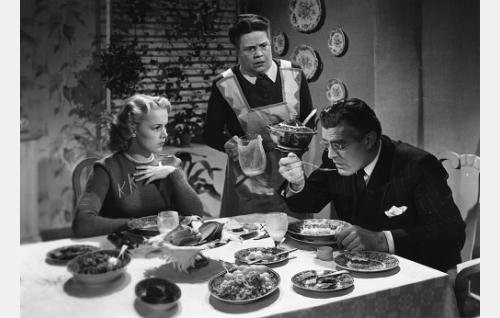 Pöydässä istumassa Kyllikki Kaarivaara (Eija Inkeri) ja hänen isänsä professori Kaarivaara (Tauno Palo), heille tarjoilee sisäkkö Elisabeth (Siiri Angerkoski).
