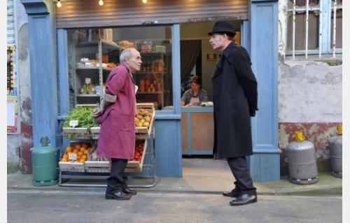 Kauppias (François Monnié) ja komisario Monet (Jean-Pierre Darroussin), taustalla kauppiaan vaimo (Valérie Caron). Kuva: Marja-Leena Hukkanen. © Sputnik Oy.