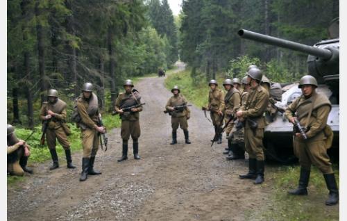 Venäläisiä sotilaita, taustalla ruumiskärryä ohjastava Eino (Joonas Saartamo). Kuva: Cine Works Koskinen & Rossi Oy.
