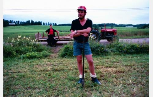Kuoppala (Tommi Korpela) aidantekopuuhissa, traktorin lavaan nojailee Rane (Puntti Valtonen).
