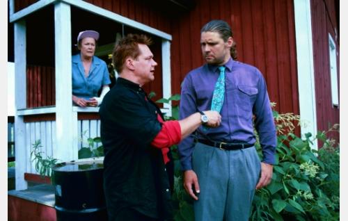 Rane (Puntti Valtonen) sättii talon ostosta kieltäytyneen grynderin (Aarni Kivinen). Kuistilla Ranen äiti (Vieno Saaristo).