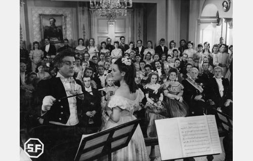 Fredrik Pacius (Thure Bahne) johtaa konserttia, laulusolistina Ebba Dunckert (Maaria Eira). Heidän välistään toiselta riviltä erottuvat Margarethe Florin (Toini Vartiainen) ja Eugen Bergfält (Toivo Ruuth), eturivissä tahtipuikon kärjen kohdalla rouva Florin (Laina Laine). Eturivissä Maaria Eirasta oikealle professori P. V. Florin (Edvin Kajanne), Nina Pacius (Aino Lohikoski), valtioneuvoksetar Martin (Kaija Suonio) ja valtioneuvos Martin (Yrjö Tuominen).