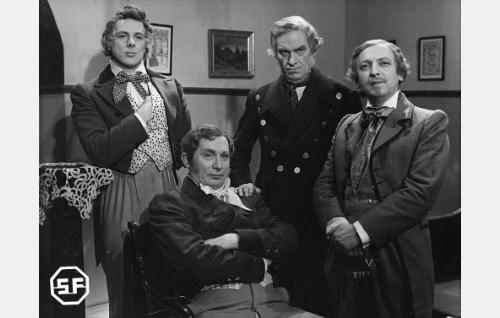 Seisomassa Fredrik Pacius (Thure Bahne), J. W. Snellman (Topo Leistelä) ja Zacharias Topelius (Arvi Tuomi). Istumassa Fredrik Cygnaeus (Kalle Rouni).