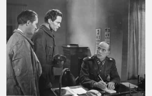 Asetoverit Janne (Vilho Auvinen, vas.) ja Eino (Eino Kaipainen) pyrkivät pois sotasairaalasta. Oikealla lääkintämajuri (Eero Leväluoma).